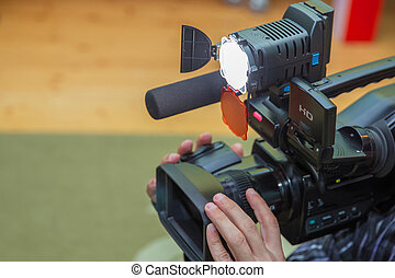 Covering an event with a video camera., Videographer takes video camera with free copy space for text., Video camera operator working with his equipment., close up of television operator with camera.