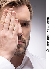 Covering eye. Portrait of confident young man covering his eye with hand while isolated on grey