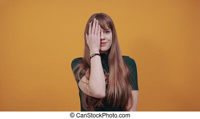 Covering eyes with hand but peeking through fingers. My eye see everything. Studio shot of sincere pretty caucasian, I can not hold promise. Charming playful. Wanting to distinguish surprise.