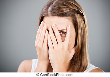 Covering face - Beautiful cheerful female covering her face...
