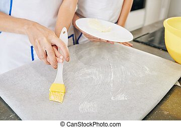 Covering parchment paper with soft butter