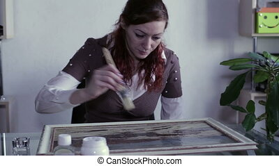 Covering picture with varnish - Woman with a brush apply a...
