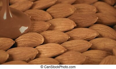 Covering raw almonds with melted chocolate slow motion shot...