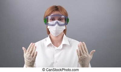 COVID-19. 2019 Novel Coronavirus 2019-nCoV concept. Female doctor, Laboratory Researcher in protective medical mask and glasses shows that all will be OK and good signs on blue rubber medical gloves