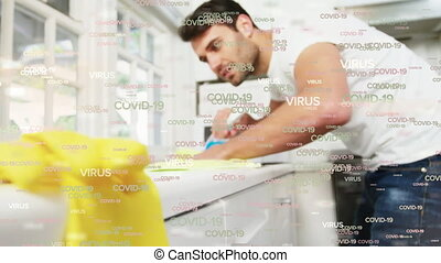 Covid-19 and virus text against man cleaning and using ...