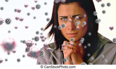 Animation of macro Covid-19 cells floating over mixed race woman praying on the white background. Coronavirus Covid-19 pandemic concept digital composite