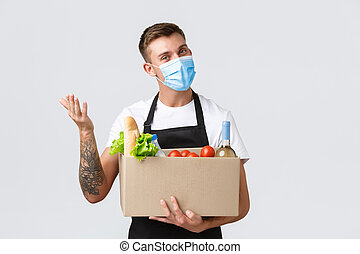 Covid-19, contactless shopping and groceries delivery concept. Friendly salesman hold box with groceries, delivering order, waving hand to say hello wearing medical mask, white background