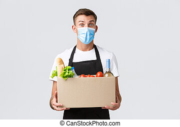 Covid-19, contactless shopping and groceries delivery concept. Handsome friendly salesman, courier in medical mask, holding grocery box from shop, selling order, white background