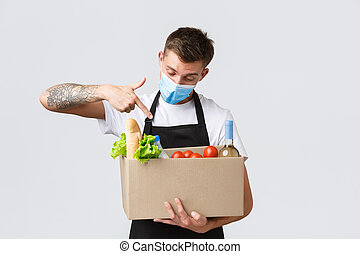 Covid-19, contactless shopping and groceries delivery concept. Handsome salesman in medical mask pointing at box with grocery order, courier handing over order to client, white background