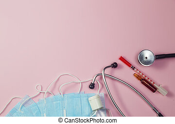 Pills, stethoscope and medical masks on pink background
