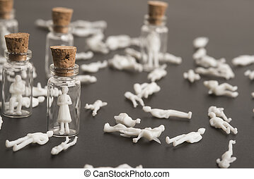 Covid-19 pandemic, coronavirus victims, old woman and people protected , concept. Figures inside glass bottles and figures scattered on the floor