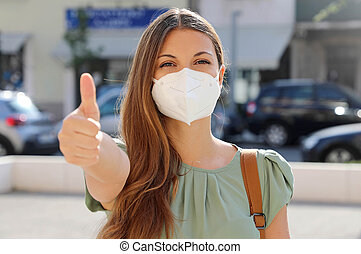 COVID-19 Positive young woman wearing protective mask KN95 FFP2 avoiding Coronavirus disease 2019 showing thumbs up in city street