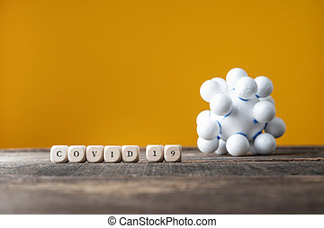 Covid 19 sign spelled on wooden dices next to a coronavirus molecule