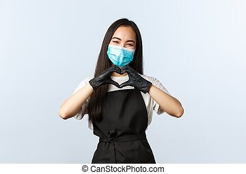 Covid-19, social distancing, small coffee shop business and preventing virus concept. Cute and tender barista, asian female cafe staff care for visitors, show heart sign, wear medical mask and gloves