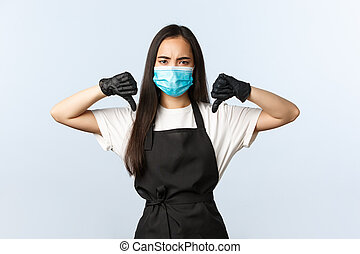 Covid-19, social distancing, small coffee shop business and preventing virus concept. Disappointed asian cafe staff, barista in medical mask and gloves show thumb-down
