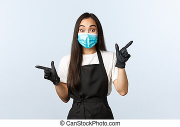 Covid-19, social distancing, small coffee shop business and preventing virus concept. Enthusiastic asian barista, cafe staff in medical mask and gloves pointing sideways, left and right
