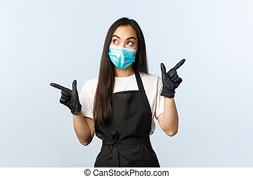 Covid-19, social distancing, small coffee shop business and preventing virus concept. Thoughtful asian barista, cafe owner in medical mask and gloves making choice, pointing sideways