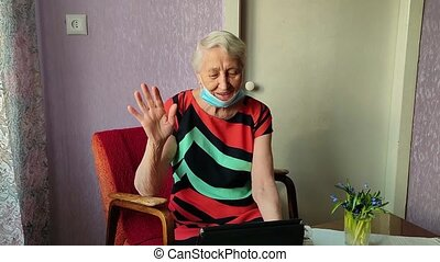 COVID-19 Stay connected. Happy senior woman at home video calling family on laptop or online chatting with long distance friends. Coronavirus lockdown, Hope, connections and technology concept.