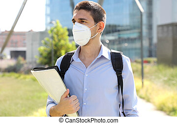 COVID-19 University student male with protective mask walking in city street. College guy back to school after pandemic.