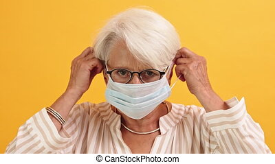 Covid19 prevention. Senior woman putting on medical mask on her face. High quality 4k footage