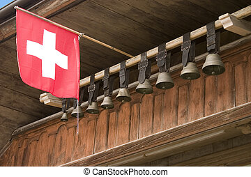 Cow bells and a Swiss flag hanging in front of Swiss chalet in Gruyeres.