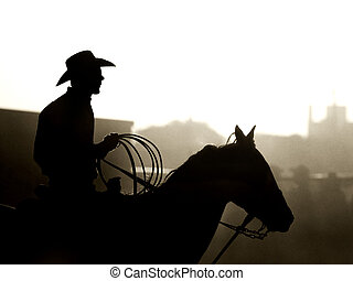 cowboy with horse and lasso, a dusty backlit silhouette. converted with added grain, shot in small town Wyoming