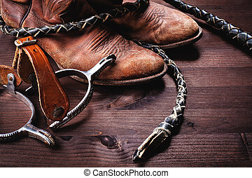 Cowboy boots,whip and spurs on wood - vintage setting, with...