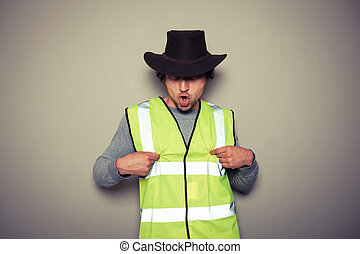 A cheeky cowboy builder is wearing a high visibility vest and twisting his nipples