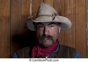 Cowboy By a Wood Wall - Close-up portrait of a cowboy with a...