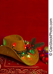 Cowboy Christmas. American West hat and bandanna on christmas red background for text