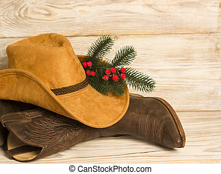 Cowboy Christmas. American West traditional boots and hat on wood background texture