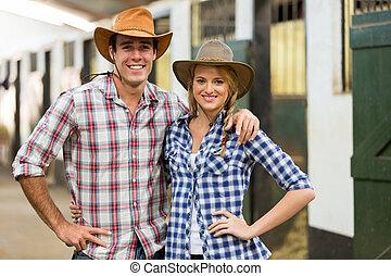 cowboy cowgirl couple inside stables - portrait of cowboy...