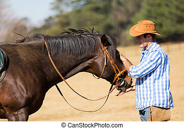 cowboy feeding his horse out of hand