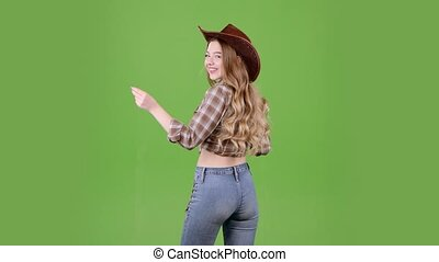 Cowboy girl dances, standing with her back to the audience. Green screen