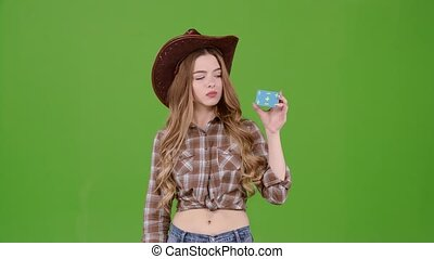 Cowboy girl in a hat and plaid shirt shows a finger down....