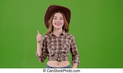 Cowboy girl in a hat shows a thumbs up. Green screen -...