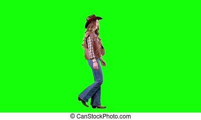Cowboy girl in a waistcoat and hat walks along the road and...