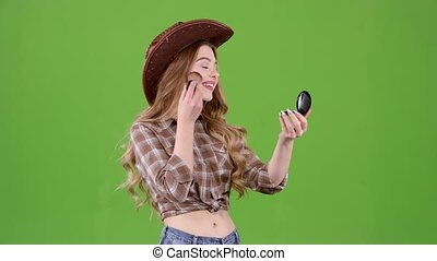Cowboy girl is holding a brush and powdering her face. Green screen