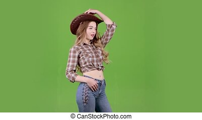 Cowboy girl puts on a hat on her head and wink. Green screen...