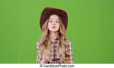 Cowboy girl sends an air kiss to her boyfriend. Green screen