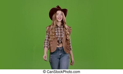 Cowboy girl sends an air kiss to her boyfriend. Green screen