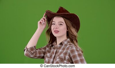 Cowboy girl sends an air kiss to her boyfriend. Green screen. Slow motion