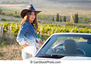 Cowboy girl stands at the white convertible