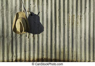 Cowboy hat against corrugated metal.