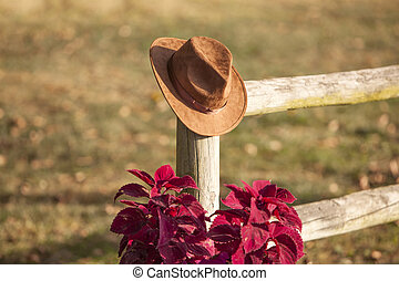 ae09147aaf7 Cowboy hat on a post. Straw cowboy hat hanging on an old wooden post.