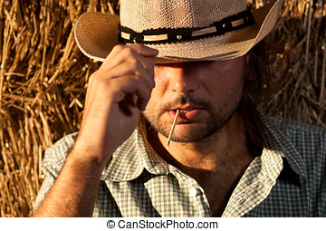 Cowboy Holding His Hat - Cowboy with Straw in His Mouth...