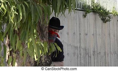 Cowboy looking through binoculars in ambush
