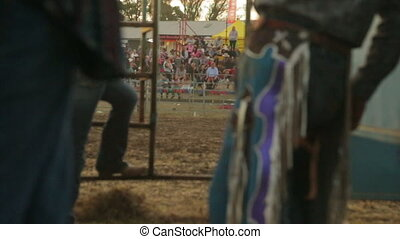 Cowboy regalia in display while people seated - A still...