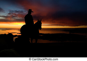 Cowboy Silhouette - A cowboy on a hill against a sunset and...