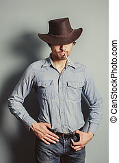 Cowboy standing by a blue wall smoking cigarette